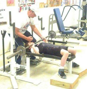Spotted by coach Daryl Haskew, Christopher Biggs practices the bench press. Photo Credit: Mark Inabinett; AL.com