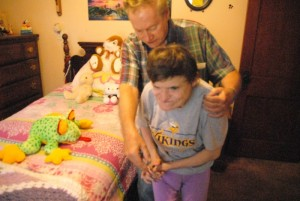 Dennis Keenan helps his daughter Vera Wilson, 50, who has cerebral palsy, around her room in West St. Paul. (Kaitlyn Roby/Review)