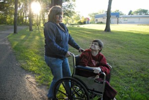 Vera Wilson, 50, who has cerebral palsy, looks up at one of her caregivers, Deb Peterson, while they walk through a park. Vera's parents have taken care of her at home her entire life. (Kaitlyn Roby/Review)